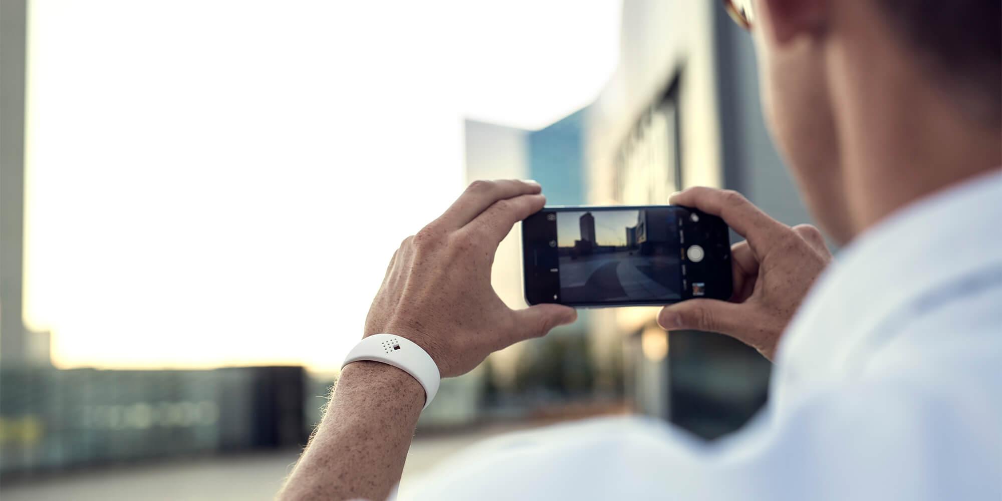 Vyras fotografuoja dėvėdamas šiuolaikinę AMBRIO apyrankę