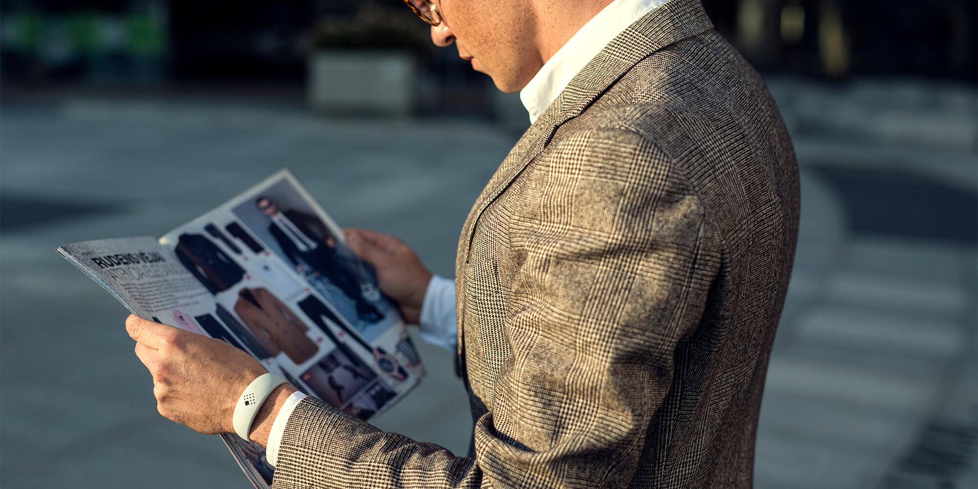 Verslininkas dėvintis prašmatnią AMBRIO apyrankę skaito mados žurnalą
