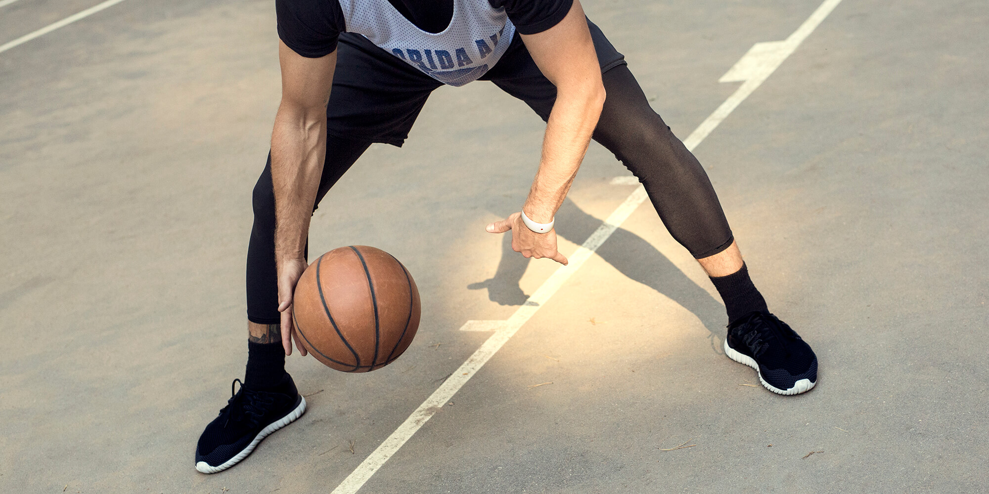 Man is playing basketball with the sleek AMBRIO bracelet