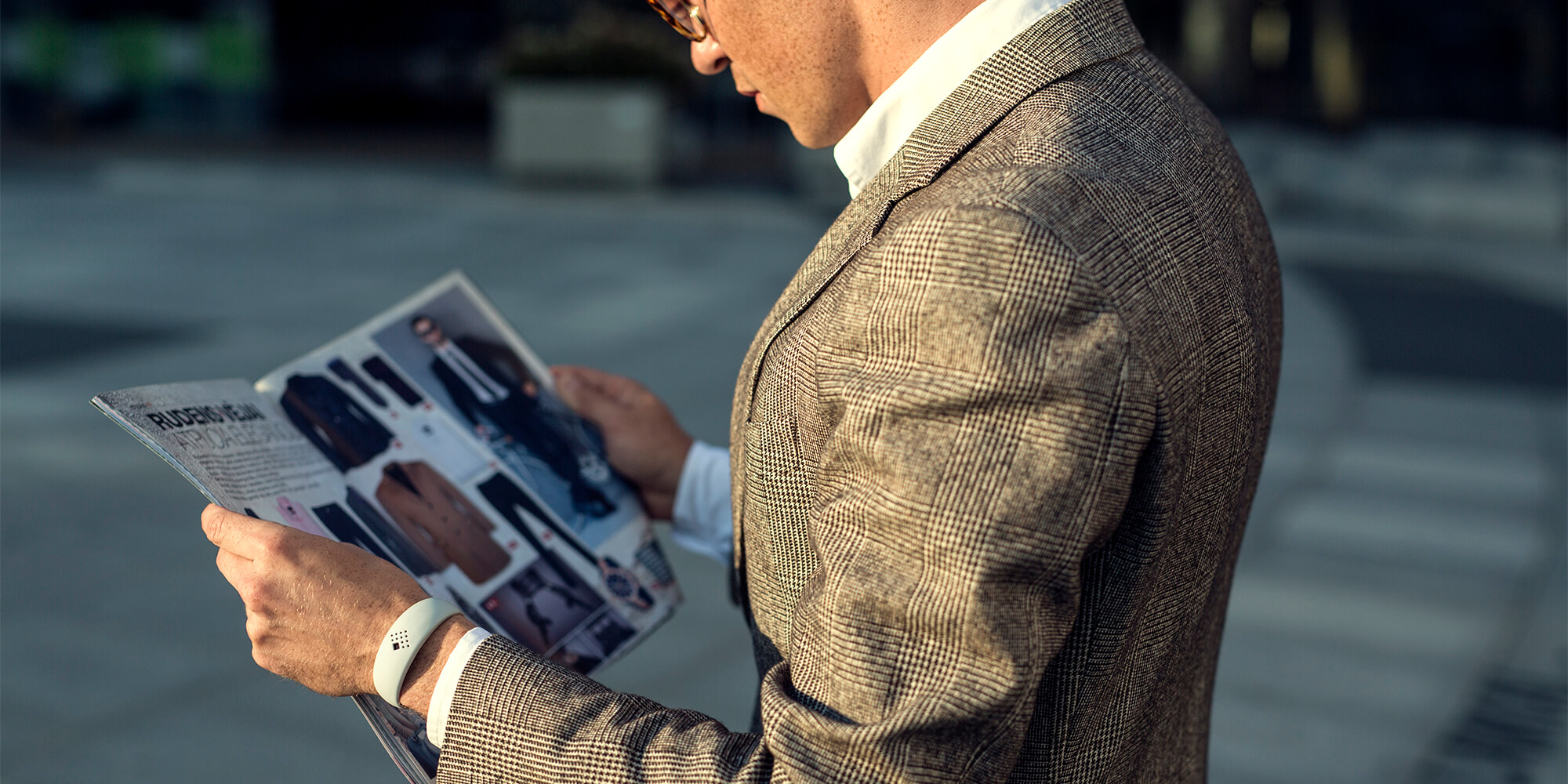 Businessman wears the luxurious AMBRIO bracelet while reading fashion magazine