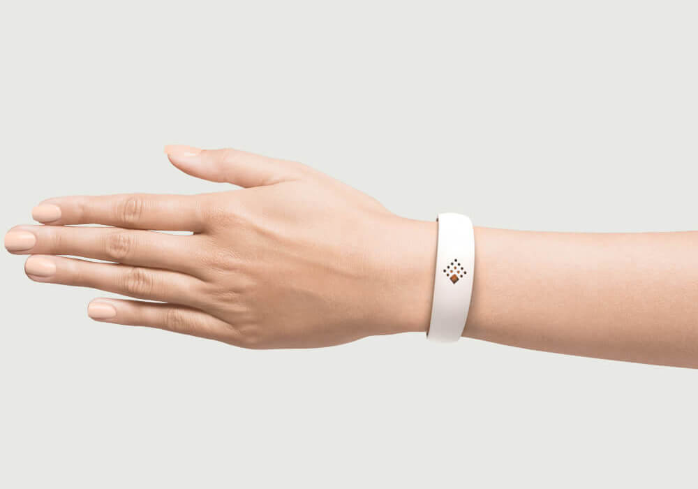 White AMBRIO bracelet on the hand of a woman for mobile