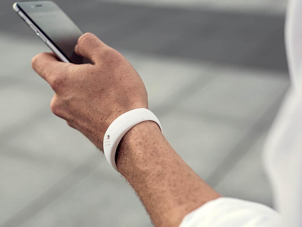 Telefoni hoidev noormees kannab trendikat AMBRIO käevõru