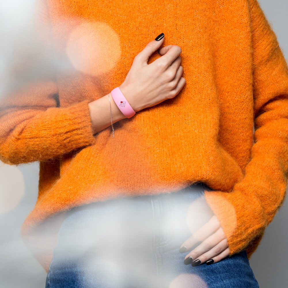 Demonstration of a pink AMBRIO bracelet with cozy sweater